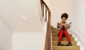 Girl reading on stairs with NEST Protect mounted to ceiling beside her