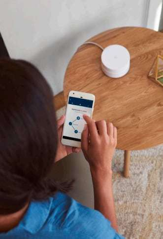 A Google Home unit on a table with woman looking at connected app