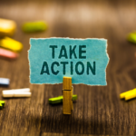 a paperclip holds a blue sign that says TAKE ACTION