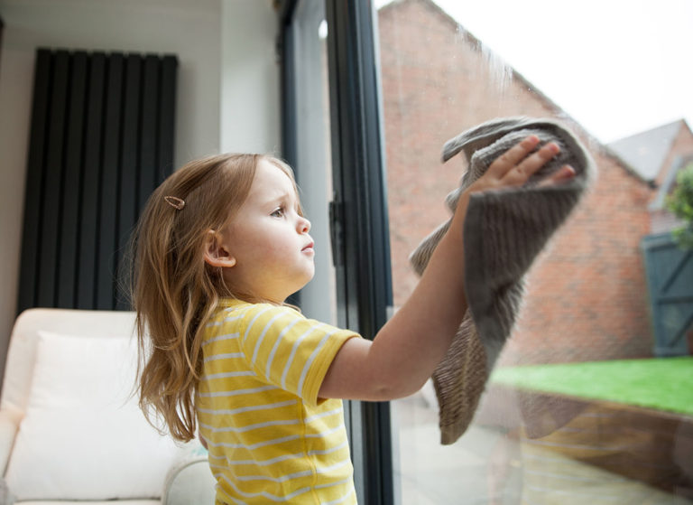 little girl cleaning window