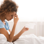 Woman in bed with headache and a tissue